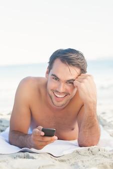 Glimlachende knappe mens op het strand die zijn cellphone houden