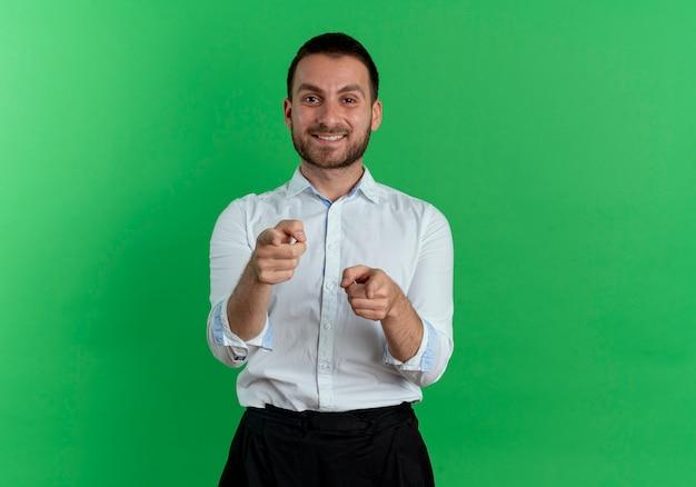 Glimlachende knappe mensenpunten met twee handen die op groene muur worden geïsoleerd