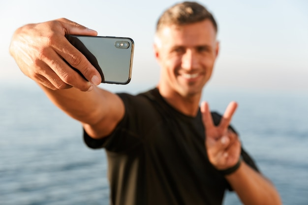 Glimlachende knappe shirtless sportman die een selfie neemt