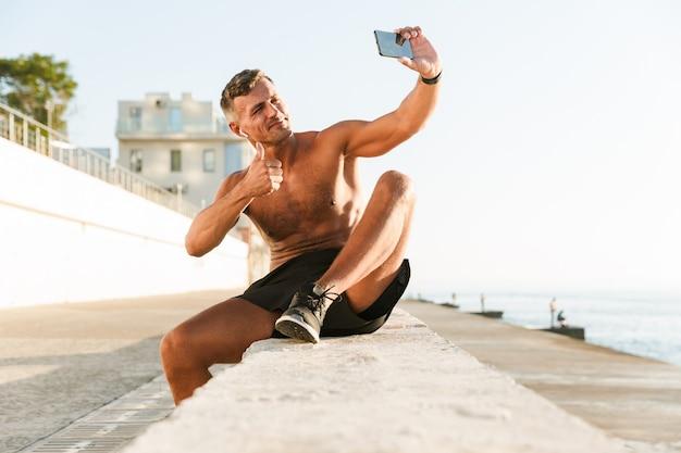 Glimlachende knappe shirtless sportman met oortelefoons