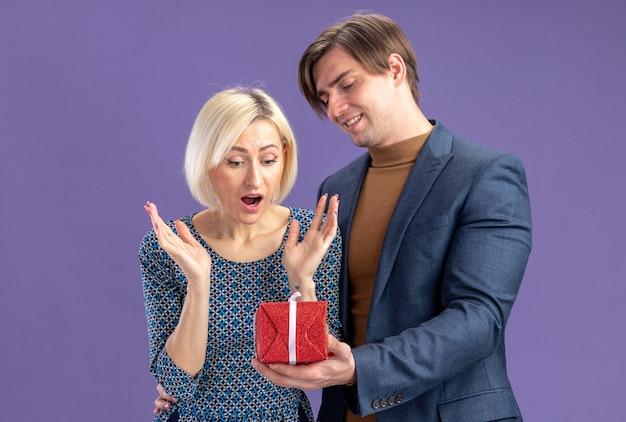 Glimlachende knappe slavische man die rode geschenkdoos geeft aan verraste mooie blonde vrouw op valentijnsdag