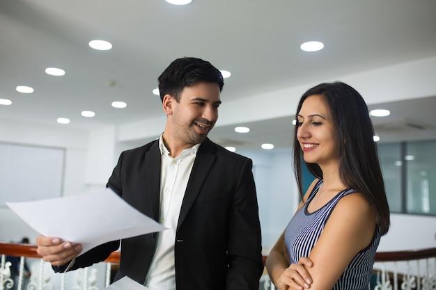 Glimlachende knappe zakenman die jaarlijks verslag toont aan collega