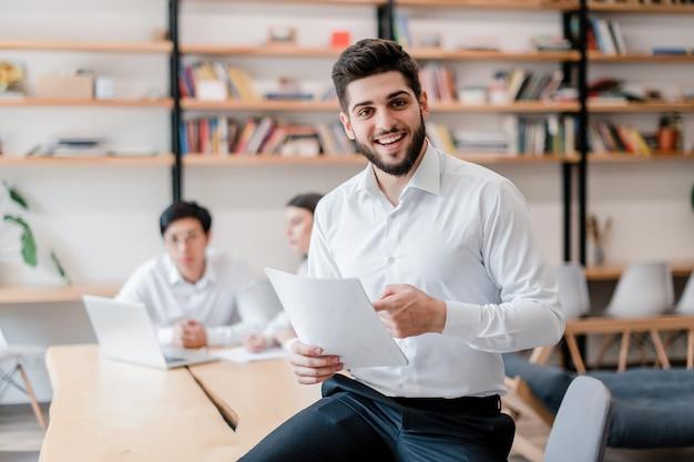 Glimlachende knappe zakenman in het kantoor