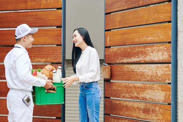 Glimlachende koerier die melk en verse boodschappen bezorgt aan vrij gelukkige jonge vrouw