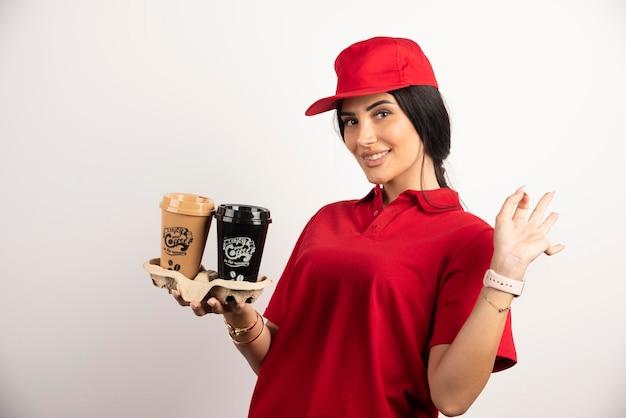 Glimlachende koerier in uniform met afhaalrestaurants koffie. hoge kwaliteit foto