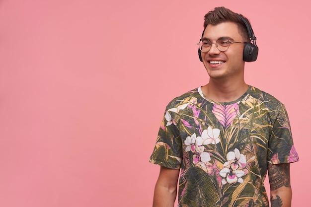 Glimlachende kortharige hansome man wegkijken, positief en in een goede bui, genietend van de muziek in de koptelefoon, poseren op roze achtergrond