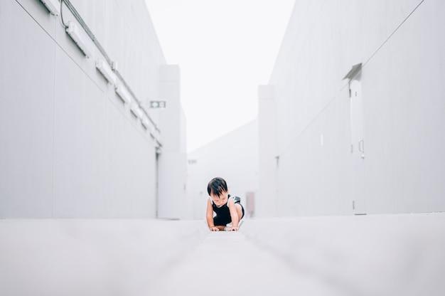 Glimlachende kruipende aziatische babyjongen bij openlucht op vloer