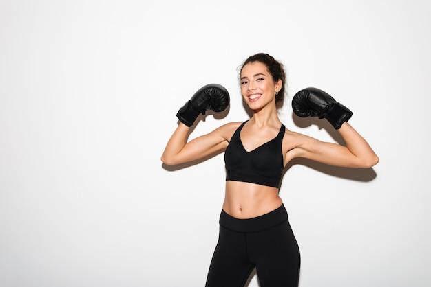 Glimlachende krullende donkerbruine geschiktheidsvrouw in bokshandschoenen die bicepsen tonen