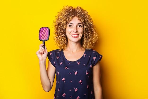 Glimlachende krullende jonge vrouw die een kam op een gele achtergrond houdt.