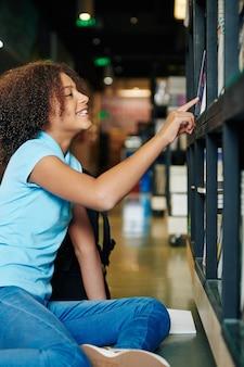 Glimlachende krullende tiener die boek van plank in bibliotheek neemt