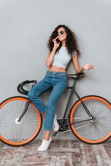 Glimlachende krullende vrouw in zonnebril die met fiets stellen en door smartphone spreken