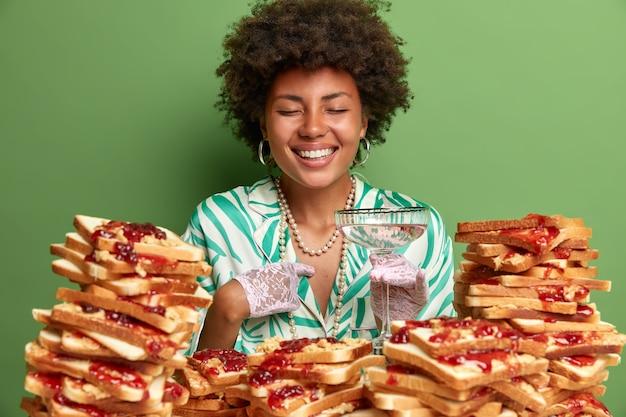 Glimlachende krullende vrouw wijst naar zichzelf, voelt zich trots en viert haar promotie, drinkt een verse cocktail, gekleed in een elegante outfit, eet veel lekkere hamburgers gemaakt van brood en jam, groene muur