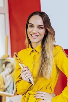 Glimlachende kunstenaar. mooie blonde-haired kunstenaar die gele blouse draagt die zich in brede zin geïnspireerd voelt