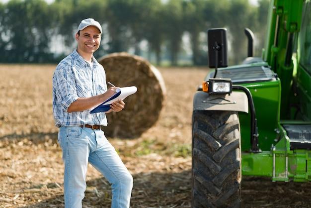 Glimlachende landbouwer die op een document schrijft