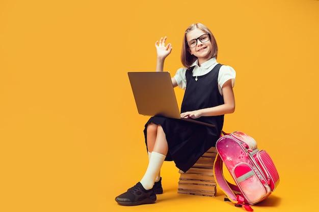 Glimlachende leerling van volledige lengte zit op de stapel boeken met laptop laat zien dat de hand zingt voor kinderen