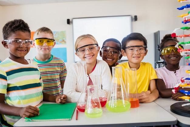 Glimlachende leerlingen die wetenschap doen