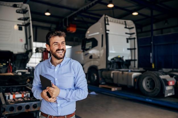 Glimlachende leider die zich in autopark bevindt en tablet houdt