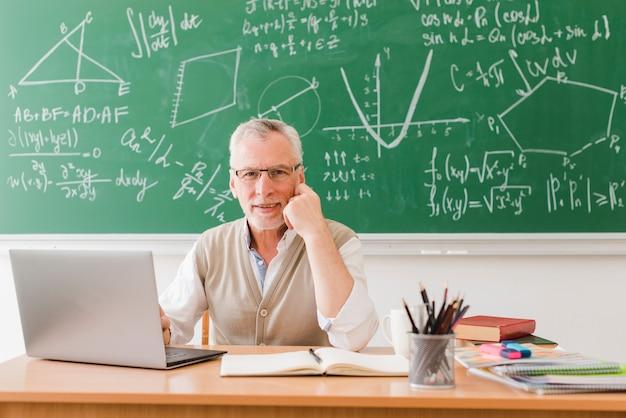 Glimlachende leraar dichtbij laptop in collegezaal