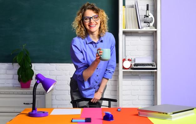 Glimlachende leraar in klaslokaal jonge vrouwelijke leraar jonge leraar in glazen over groen bord