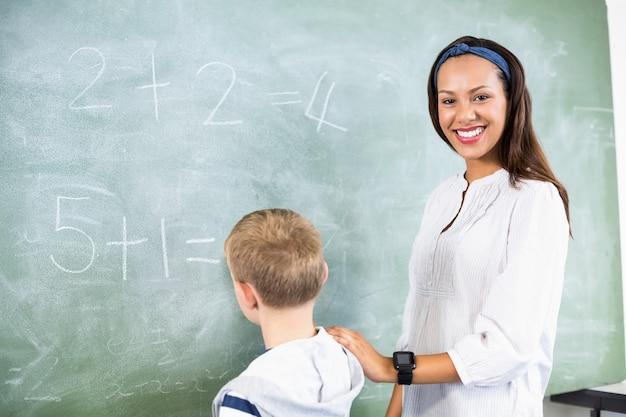 Glimlachende leraars bijwonende jongen in het doen van toevoeging op bord