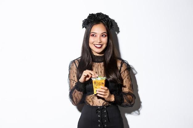 Glimlachende leuke aziatische vrouw die halloween viert, snoepjes houdt en gelukkig grijnst, trick or treat in heksenkostuum