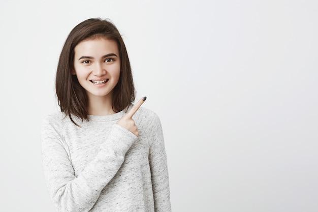 Glimlachende leuke europese vrouw met vrolijke blik, wijzend op corne rechtsboven