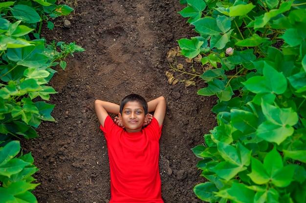 Glimlachende leuke indische jongen die op grond legt