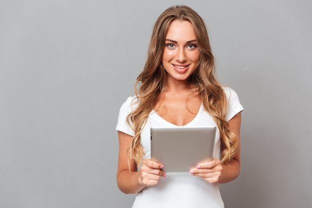 Glimlachende leuke jonge vrouw die tablet over grijze muur met behulp van