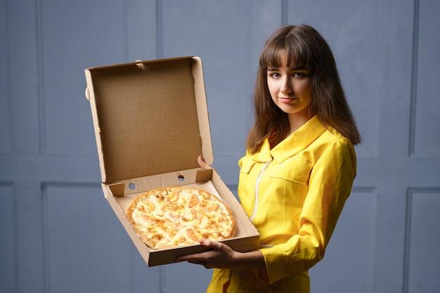 Glimlachende leuke jonge vrouw in een gele jumpsuit die pizza levert.