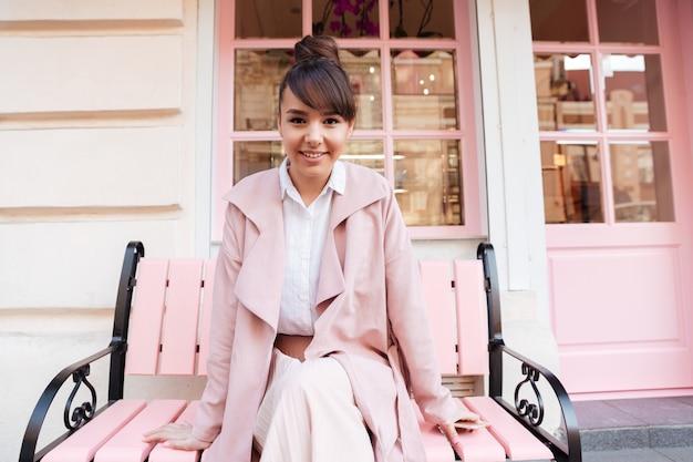 Glimlachende leuke jonge vrouw in roze jas zittend op de bank