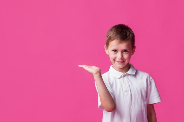 Glimlachende leuke jongen die op roze achtergrond voorstelt