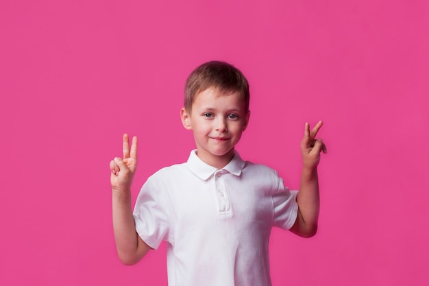 Glimlachende leuke kleine jongen die overwinningsteken op roze achtergrond toont