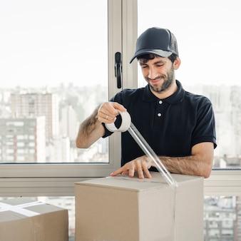 Glimlachende leveringsmens in de eenvormige doos van het verpakkingskarton