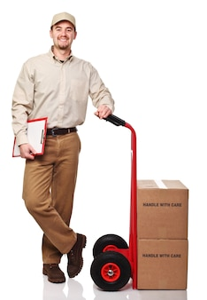 Glimlachende leveringsmens met rode handtruck die op wit wordt geïsoleerd