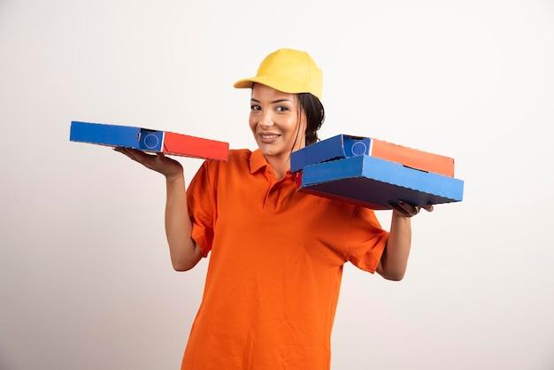 Glimlachende leveringsvrouw die pizzadozen op witte muur houdt.
