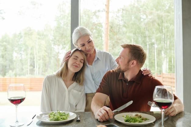 Glimlachende liefdevolle senior moeder omhelst dochter en haar man terwijl ze haar in landhuis bezoeken