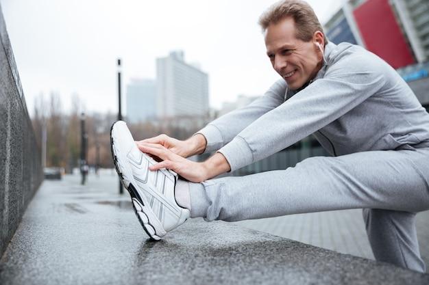 Glimlachende loper in grijze sportkleding die op straat aan het opwarmen is. zijaanzicht