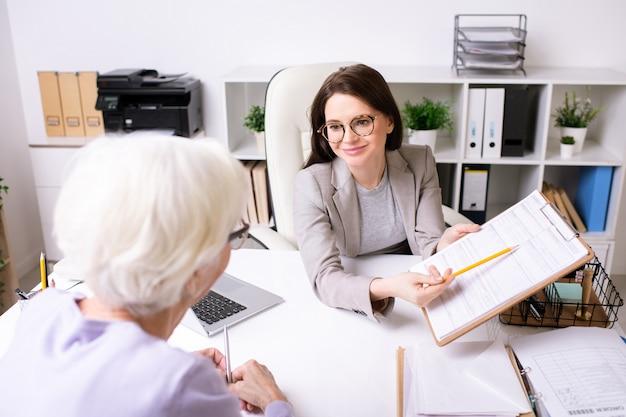 Glimlachende maatschappelijk werker in gesprek met gepensioneerde vrouw en het presenteren van informatie aan haar tijdens de vergadering