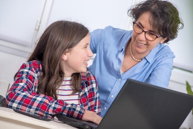 Glimlachende mamma en dochter die laptop thuis met behulp van