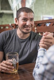 Glimlachende man arm worstelen met vriend in bar