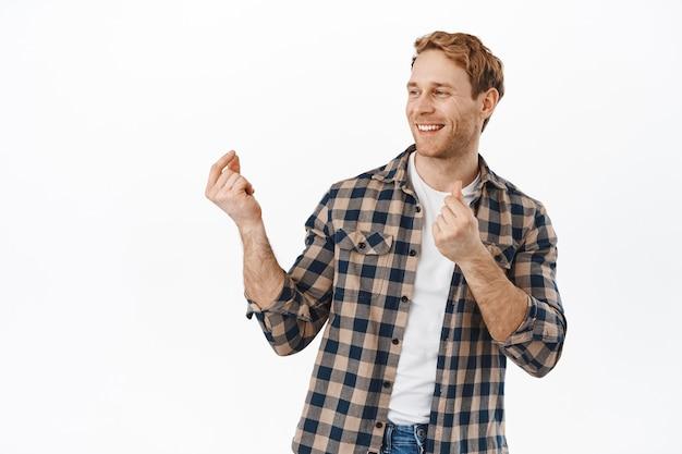 Glimlachende man danst en knipt met de vingers en heeft plezier, danst en ziet er gelukkig uit, draai het hoofd opzij naar de promotietekst van het logo, staande over een witte muur