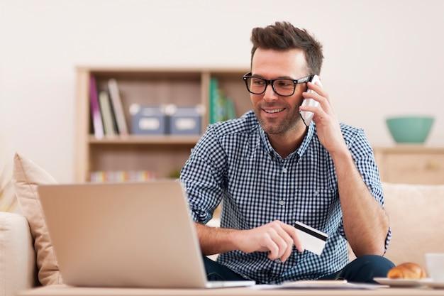 Glimlachende man die bestelling plaatst via de mobiele telefoon