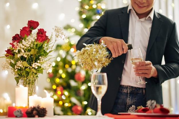 Glimlachende man die champagne in fluit giet als hij aan de kersttafel staat