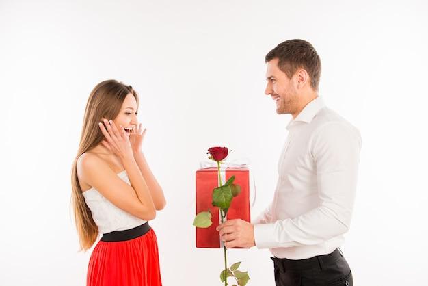 Glimlachende man die een geschenk en een roos geeft aan zijn vriendin