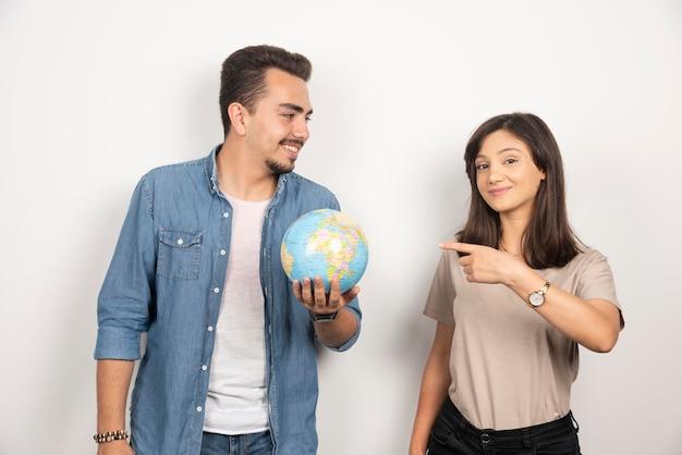 Glimlachende man die een wereldbol houdt en op meisje kijkt.