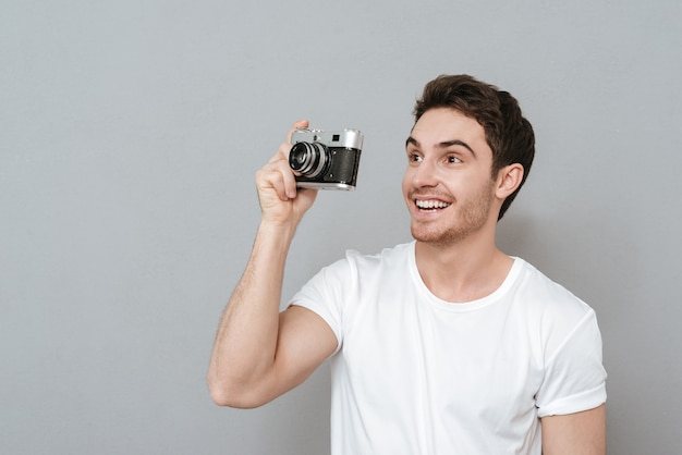 Glimlachende man die foto maakt op retro camera. zijaanzicht. geïsoleerde grijze muur