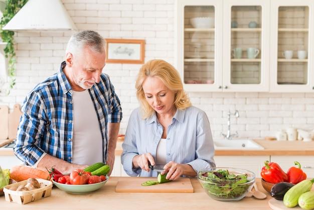Glimlachende man die haar vrouw bekijkt die de komkommer met mes op lijst in de keuken snijdt