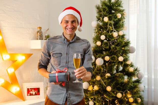 Glimlachende man die kerstcadeaus thuis opent