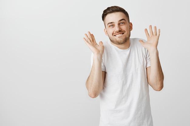 Glimlachende man die liegt weet niets, steekt zijn handen op met een sluwe grijns
