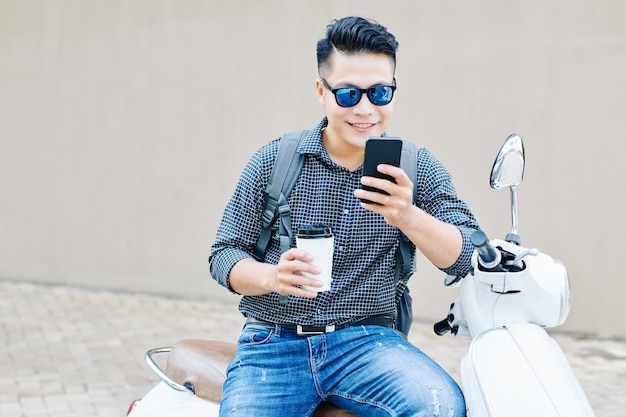 Glimlachende man die meldingen op smartphone controleert